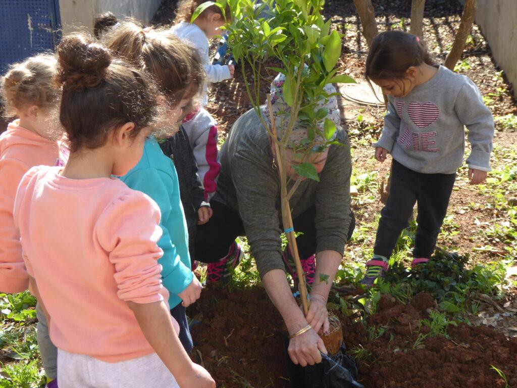 Daghemsbarn och en pedagog planterar ett träd
