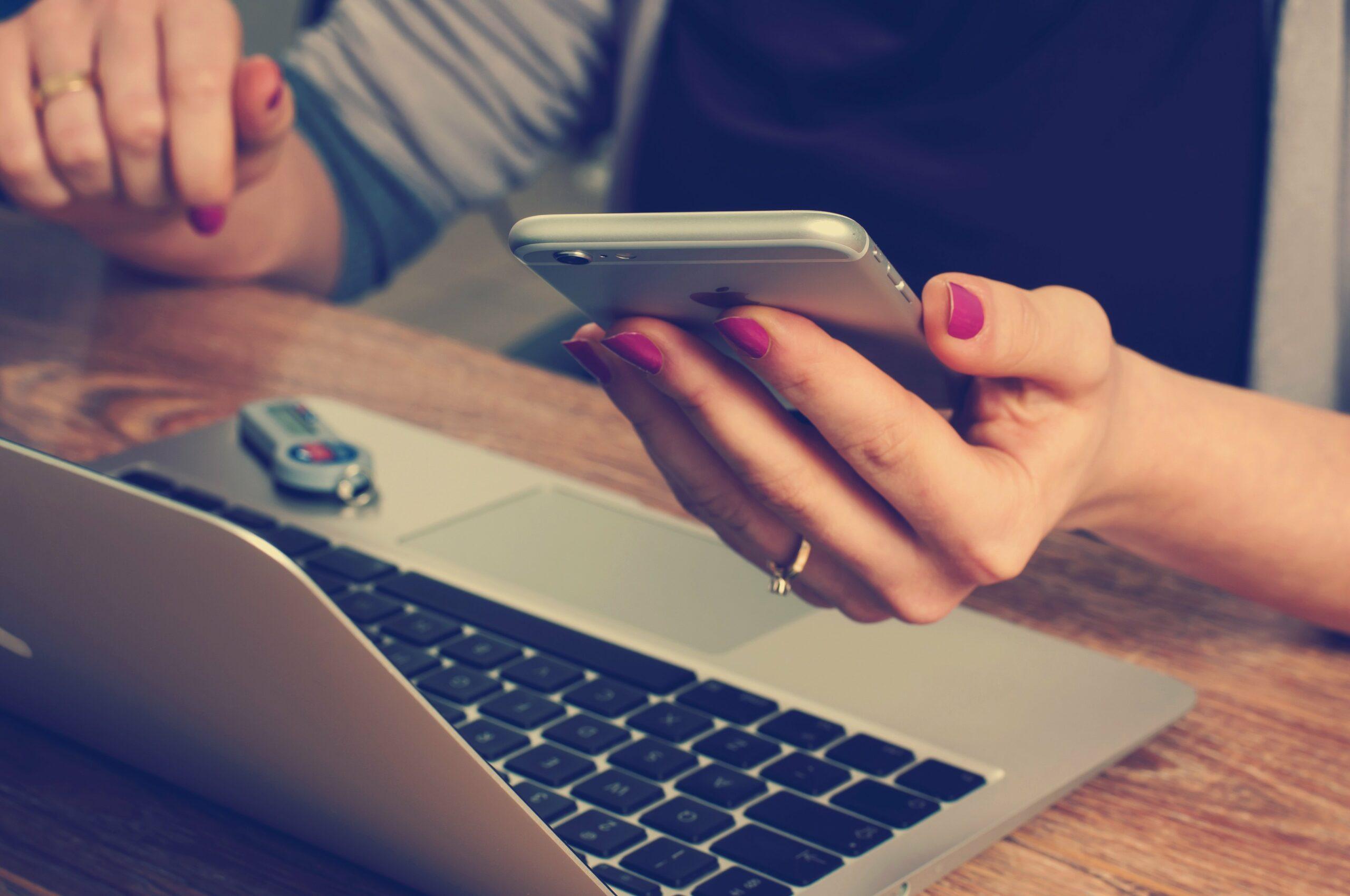Kvinna arbetar med laptop och mobiltelefon