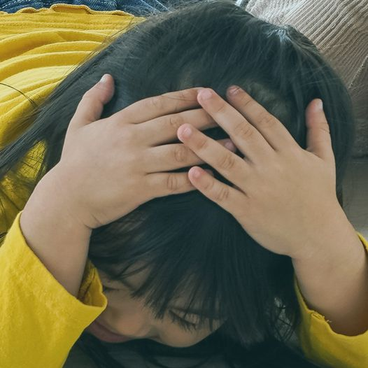 Skrämd flicka håller för huvudet